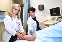 Dr. Andrea Hendrzak, Director, Endovascular and Venous Surgery (left), and Valeriya Basin, Vascular Lab Coordinator, Surgery, providing vein care to patient.