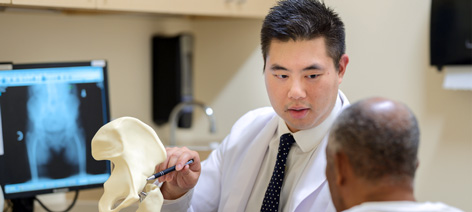 Dr. Ronald Huang, Attending, Joint Replacement Surgery, discussing surgical options with patient.
