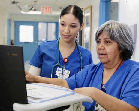 (L to R): Ana Martinez, RN, and Alicia Rojas, RN, reviewing patient information.