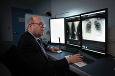 Dr. Harvey Stern, Attending, Radiology, interpreting multiple X-rays.