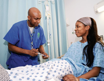 Rudolph Toussaint, RN, attending to patient on Family Medicine Unit.