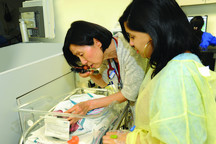 Dr. Mae Hee Kim, Attending, Neonatology, examining newborn in NICU, as mother looks on.