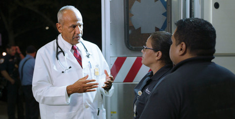 Dr. Charles Martinez, Medical Director, EMS, in ER ambulance area, with Emergency Medical Technicians.