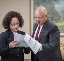 Octavio Marin, Vice President, Long Term Care/Ambulatory Care Services, reviewing schedule with Michelle Aguirre-Calderon, Executive Secretary.