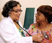 Dr. Yvonne Cruz, Medical Director, BronxCare Medical and Dental Practice at Poe, examining patient.